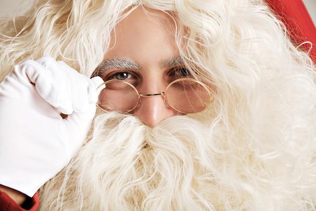 Feche o retrato do papai noel com luvas brancas ajustando seus óculos de aro dourado