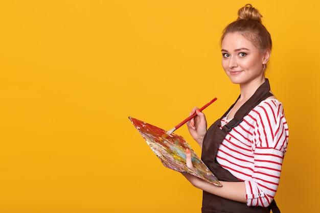 Feche o retrato do perfil da artista feminina feliz, segurando a paleta e o pincel nas mãos, de pé contra o amarelo