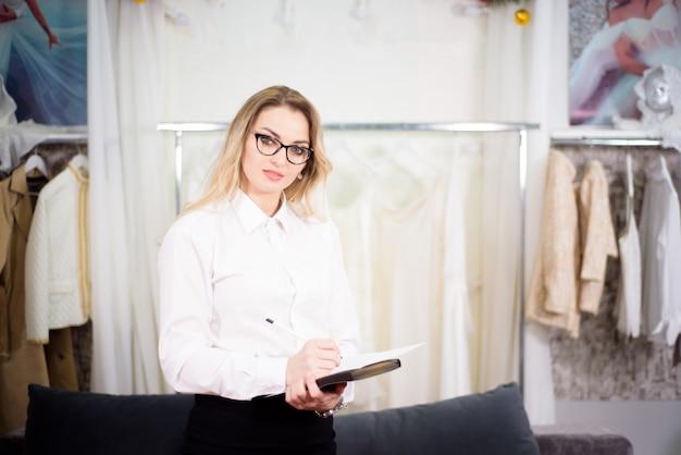 Feche o retrato do tiro na cabeça do estilista de moda mulher caucasiana bem sucedida sorridente ou alfaiate pose no escritório.