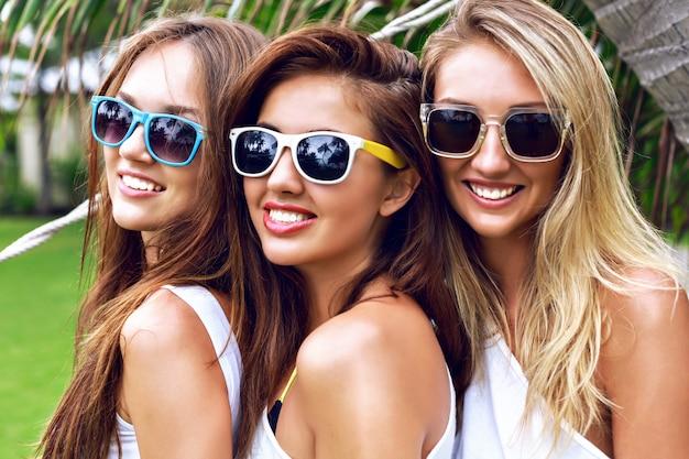 Feche o retrato do verão da árvore jovem mulher bonita sexy, vestindo tops brancos na moda casuais simples e óculos de sol brilhantes, sorrindo, se divertindo nas férias no país tropical.