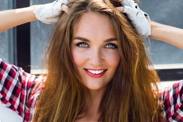Feche o retrato ensolarado do estilo de vida da moda do verão da incrível jovem bonita com sardas, maquiagem sexy brilhante e cabelos longos fofos.