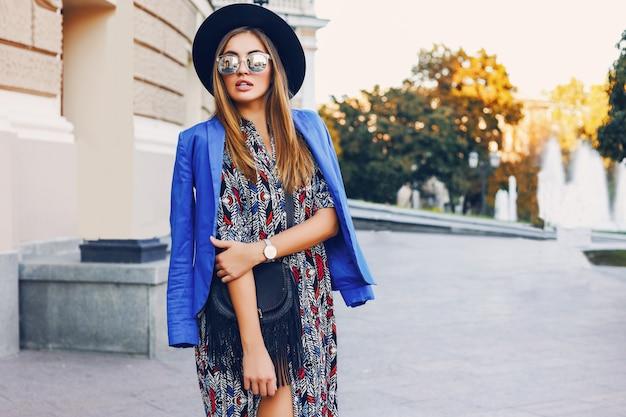 Feche o retrato ensolarado do estilo de vida da mulher casual elegante de chapéu preto, vestido brilhante e casaco azul nos ombros, andando nas ruas da europa. moda e conceito de compras.