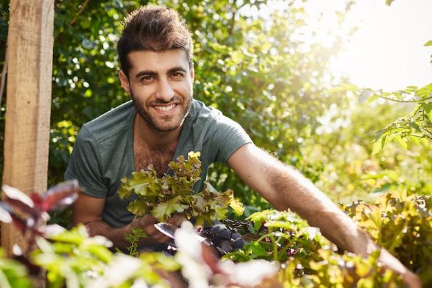 Feche o retrato externo de uma jovem bela barbudo homem hispânico na camisa azul, sorrindo para a câmera, coletando folhas de salada no jardim, regando plantas, passando a manhã de verão em uma casa de campo.