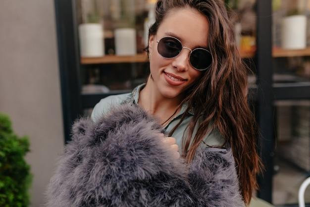 Feche o retrato externo de uma jovem encantadora usando pele e óculos elegantes, posando para a câmera