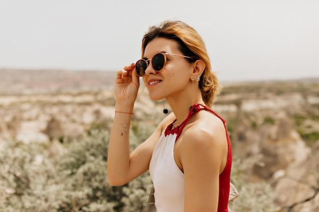 Feche o retrato externo de uma mulher espetacular tocando os óculos e olhando para o lado com um sorriso na paisagem montanhosa