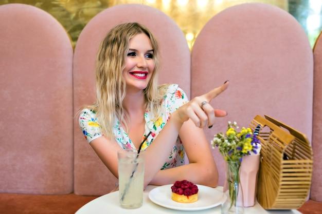 Feche o retrato interior do estilo de vida de uma mulher loira bonita posando no restaurante, comendo um bolo saboroso e mostrando algo por seu dedo, interior feminino bonito, emoções alegres.
