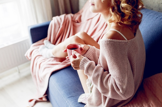 Feche o retrato interno de graciosa mulher loira, apreciando o cheiro de cappuccino, sonhando e olhando pela janela. vestindo uma camisola de malha rosa.