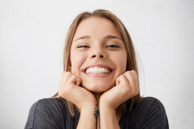 Feche o retrato interno de mulher jovem e feliz, comemorando o sucesso e a promoção no trabalho, olhando com um largo sorriso alegre, segurando o rosto com as mãos, sentindo alegria e felicidade