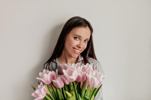 Feche o retrato interno de uma garota feliz e sorridente com maquiagem nude e longos cabelos escuros posando com flores sobre uma parede branca