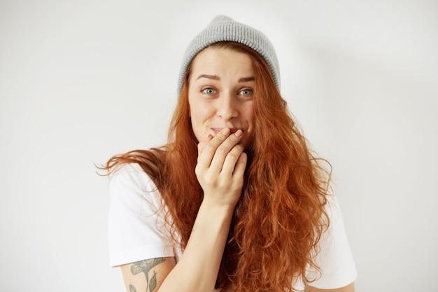 Feche o retrato isolado de uma jovem ruiva rindo, cobrindo a boca com a mão