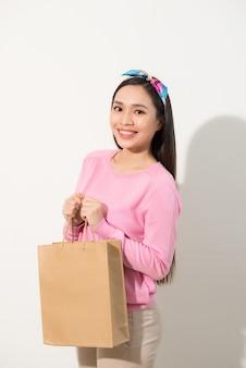 Feche o retrato jovem bonita atraente sorrindo com uma sacola de compras marrom. parede branca. copie o espaço.