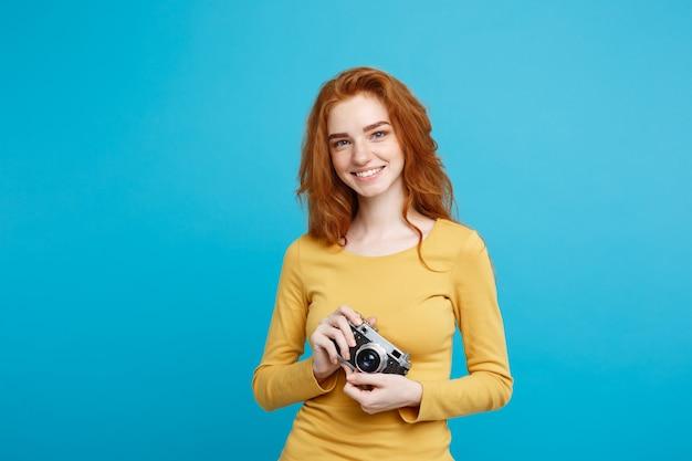Feche o retrato jovem bonita e atraente ruiva feliz sorrindo com uma câmera vintage e pronta para viajar, isolada no espaço de cópia da parede azul pastel