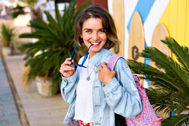 Feche o retrato positivo de mulher elegante hippie posando em frente ao local de surf, roupa da moda jovem, óculos de sol azuis, jaqueta jeans e mochila, palmeiras ao redor.