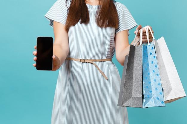 Feche o retrato recortado de mulher com vestido de verão segurar pacotes sacos com compras após as compras, celular móvel com tela vazia, isolada em fundo azul pastel. copie o espaço para anúncio