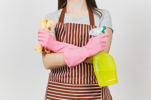 Feche o retrato recortado dona de casa em luvas cor de rosa, avental listrado, isolado no fundo branco. mulher de mãos cruzadas, borrifador com pano de limpeza líquido mais limpo. copie o espaço para anúncio