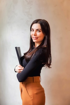Feche o retrato sorridente administrador de mulher de negócios jovem no fundo da parede cinza texturizada. gerente feminina em pé e olhando para a câmera. seus braços cruzados com pasta de documentos e sorrisos