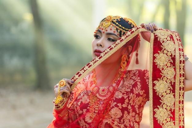 Feche o rosto da índia. mulher asiática jovem retrato de vestido vermelho indiano.