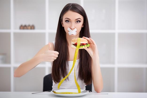 Feche o rosto da jovem e bela mulher latina triste com a boca selada na fita adesiva