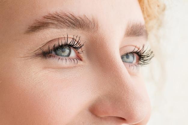 Feche o rosto de uma bela jovem caucasiana, concentre-se nos olhos