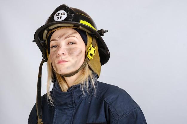 Feche o rosto de uma jovem corajosa de uniforme, capacete de bombeiro l