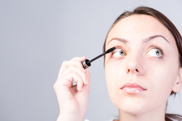 Feche o rosto de uma jovem mulher aplicando maquiagem rímel enquanto olha para a direita em um fundo cinza.