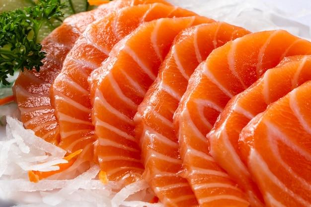 Feche o sashimi de salmão em um prato branco.
