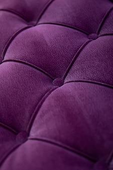 Feche o sofá moderno de tecido de veludo roxo texturizado com botões afundados. idéia e variante de tecido para estofamento de sofá.