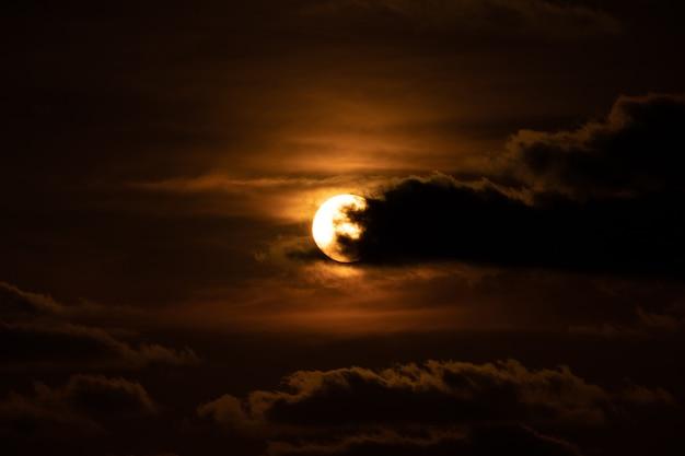 Feche o sol com uma nuvem na frente dele na hora do crepúsculo do pôr do sol.