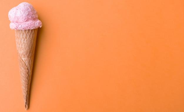 Feche o sorvete de morango no cone de waffles em fundo laranja. copie o espaço.