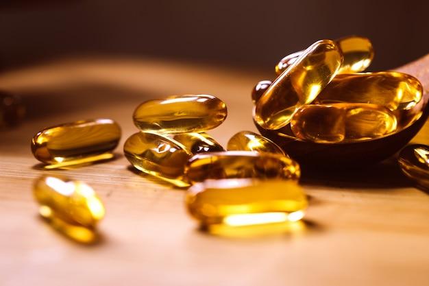 Feche o suplemento de cápsulas de óleo de peixe de vitamina d e ômega 3 na placa de madeira para obter um bom benefício alimentar do cérebro, coração e saúde