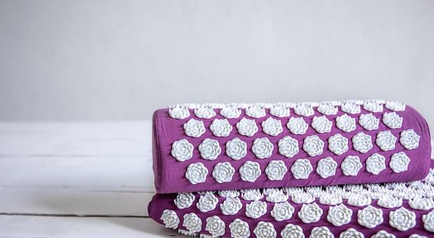 Feche o tapete de acupuntura de massagem com travesseiro e dicas de massagem brancas, tapete de massagem para relaxamento e tratamento.