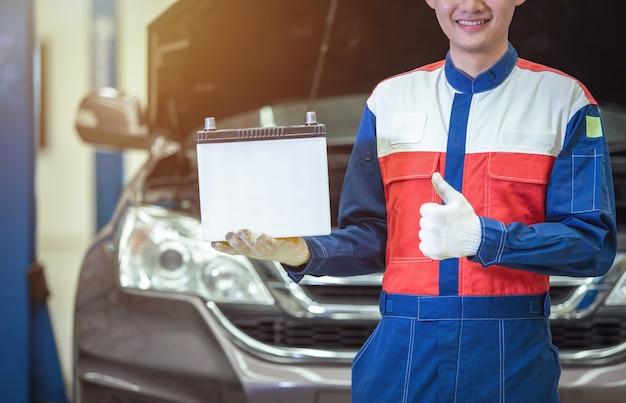 Feche o técnico de mão ou mecânico de automóveis tranquilizando a bateria do carro no centro de serviço de reparo de automóveis.