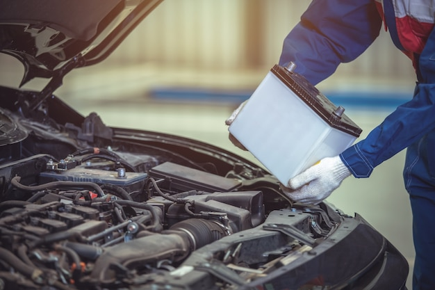 Feche o técnico de mão ou mecânico de automóveis, troque a bateria do carro no centro de serviço de reparo de automóveis.