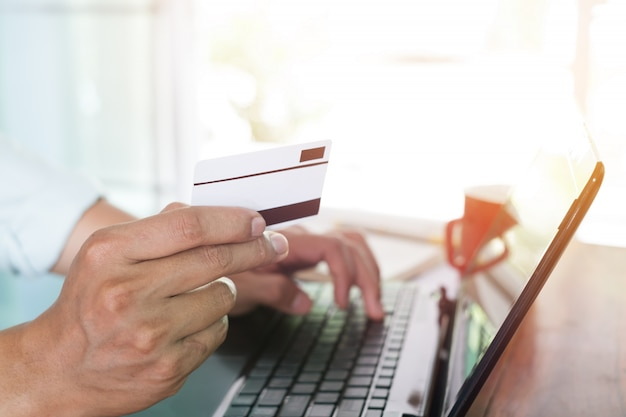 Feche o tiro ao lado do jovem empresário trabalhando em seu laptop e usando o cartão de crédito sentado na mesa de madeira em um café com tom de cor de filtro vintage