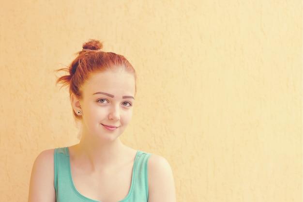 Feche o tiro da moça bonita sem fazer as pazes com o cabelo vermelho amarrado no coque