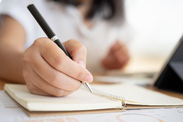 Feche o tiro das mãos da empresária segurando uma caneta escrevendo algo