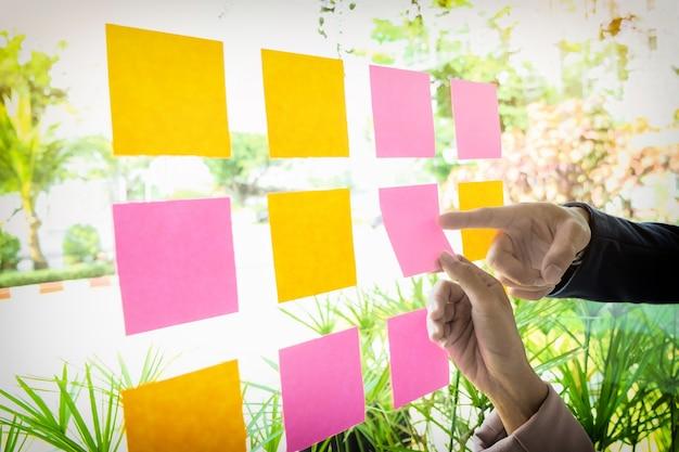 Feche o tiro das mãos da mulher que cola as notas adesivas na parede de vidro no escritório