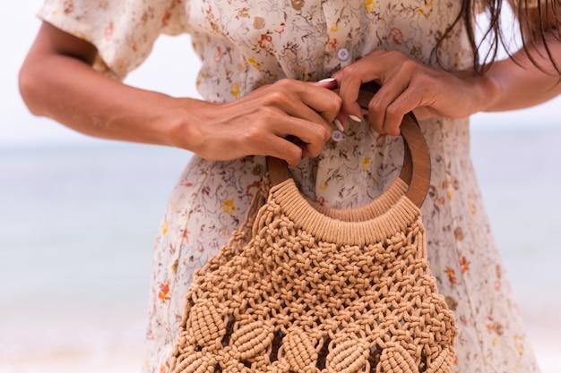 Feche o tiro de mulher com vestido voador de verão leve segurando uma bolsa de malha na praia, mar no fundo.