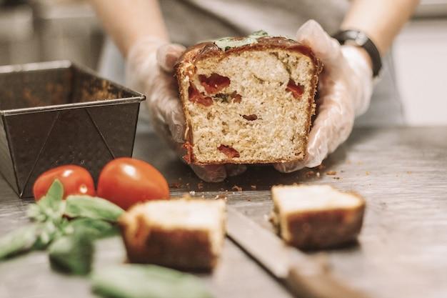 Feche o tiro do chef segurando um pedaço de pão perto de tomates com um fundo desfocado
