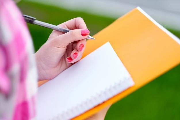 Feche o tiro do estudante, mão de uma mulher escrevendo algo sobre o papel em primeiro plano. pesquisas de opinião ou conceito de estatísticas.
