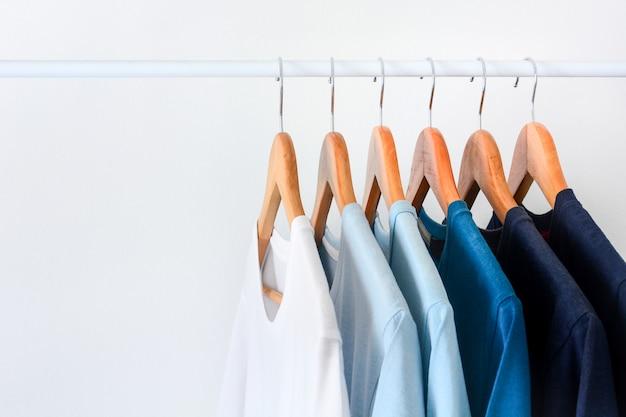 Feche o tom da coleção de camisetas de cor azul, penduradas no cabide de madeira