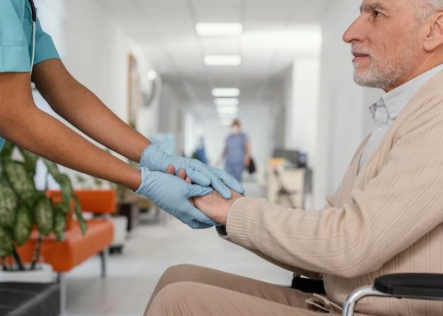 Feche o trabalhador de saúde ajudando o paciente