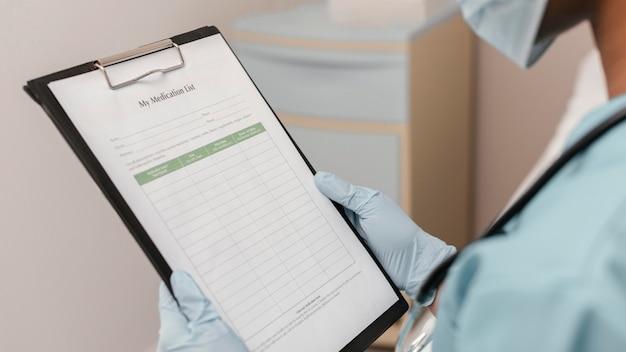 Feche o trabalhador de saúde verificando a lista de medicamentos