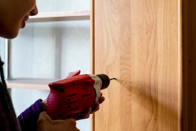 Feche o trabalhador fazendo um buraco na superfície de madeira em casa usando a broca f
