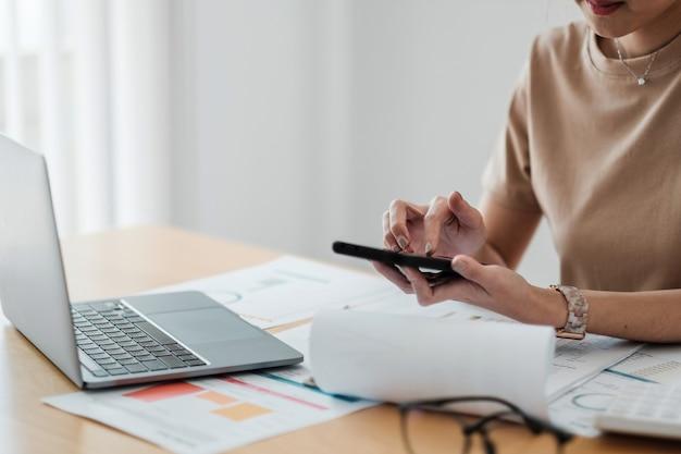 Feche o trabalho feminino jovem com papéis financeiros em casa, conte na calculadora antes de pagar os recibos de impostos online por telefone.