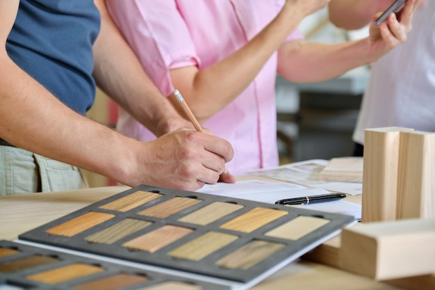 Feche o trabalho na oficina de móveis de carpintaria, mãos de trabalhadores, paleta de móveis de madeira
