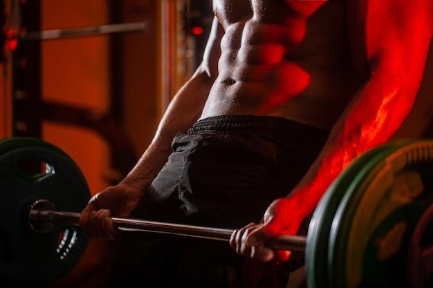 Feche o treinamento com barra. homem levantando halteres malhando no ginásio. treino de halteres closeup deadlift. homem desportivo levanta a barra no ginásio. faça exercício no ginásio. homem atlético com tanquinho, abs perfeito.