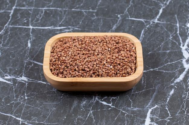 Feche o trigo mourisco cru em uma tigela de madeira. grão antigo sem glúten para uma dieta saudável.