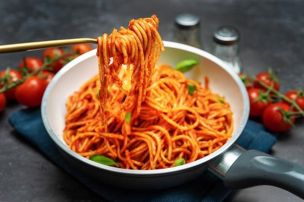 Feche o uo do garfo com espaguete em molho de tomate