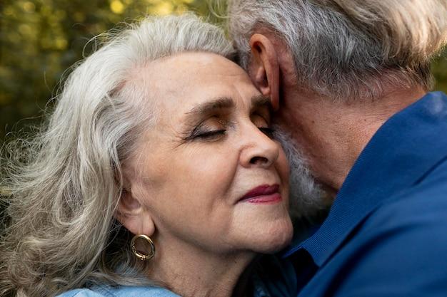 Feche o velho casal se abraçando na natureza
